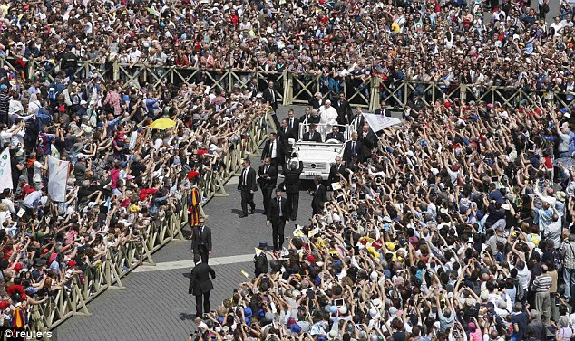Pope Francis, wearing a plain white cassock, climbed into an open white popemobile to ride up and down the security paths surrounding the crowd of more than 60,000