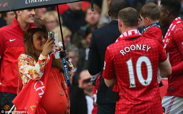 Wayne Rooney of Manchester United has his picture taken by his wife Coleen
