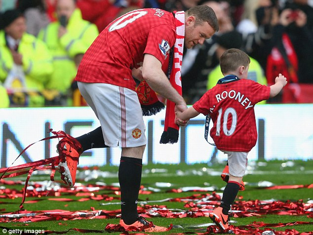 Wayne Rooney of Manchester United walks with his son Kai
