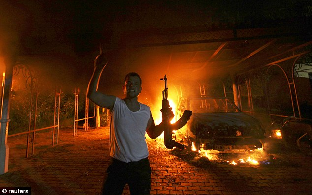 A protester reacts as the U.S. Consulate in Benghazi is seen in flames during an attack on the U.S. Consulate in the city