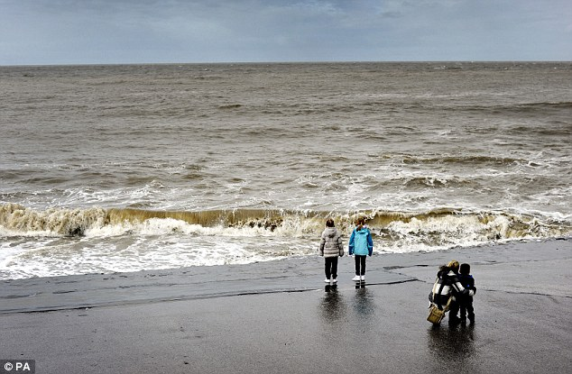 Looking out: A bleak day on the seaside at Porthcawl in south Wales as winds of up to 65mph battered British coastlines during the night resulting in trees blown down, in what was unusual weather for May