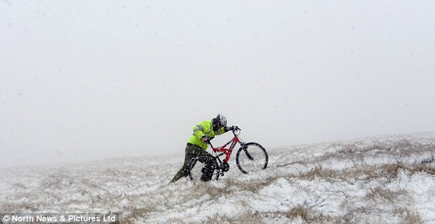 Hard work: A cyclist pushes their bicycle up a hill in the Pennines in Cumbria amid snow blizzards