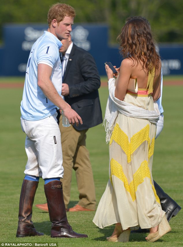 Celebrating: Harry relaxes with a female bystander after the end of the polo match