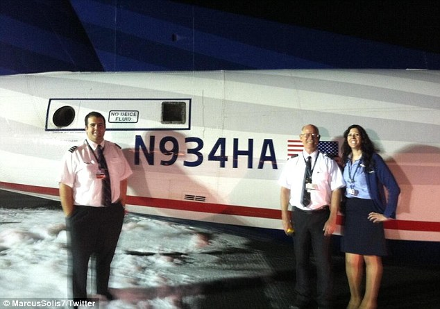 Relieved: Pilot Ed Powers poses alongside his co-pilot and a member of the cabin crew after the emergency landing
