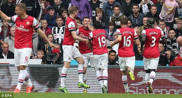 Mobbed: Arsenal team-mates Aaron Ramsey, Santi Cazorla and Bacary Sagna join Koscielny to celebrate