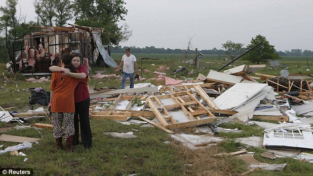 Nothing left: Leah Hill, pictured left, of Shawnee, Oklahoma, is hugged by friend Sidney Sizemore, as they look through Hill's scattered belongings from her home which was wrecked by a tornado