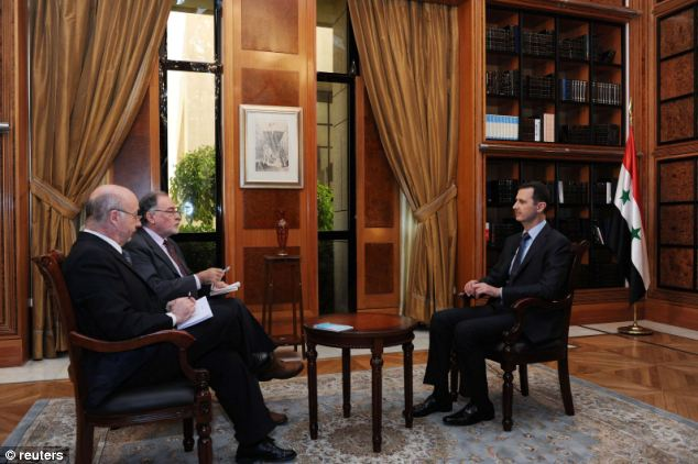 Interview: Syria's President Bashar al-Assad (right) sits during an interview with journalists from Argentina in Damascus in this handout photograph distributed by Syria's national news agency