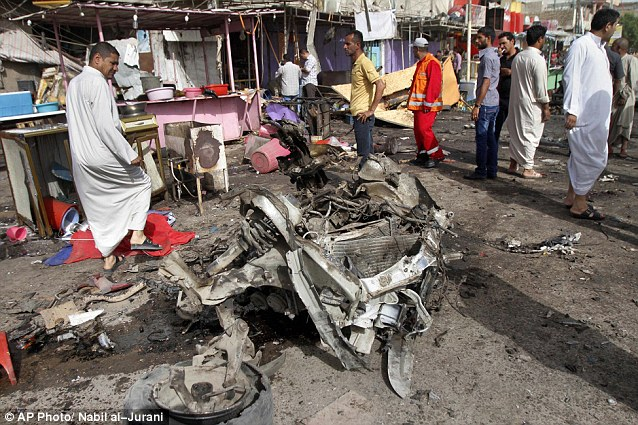 Wreckage: Civilians gather at the site of a car bomb attack in front of a crowded restaurant in Basra in southeast Iraq. Two car bombs left dozens killed and injured in the city today