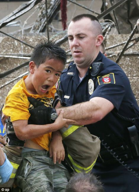 Brave: A boy is pulled from beneath a collapsed wall at the Plaza Towers Elementary School following a tornado in Moore, Oklahoma