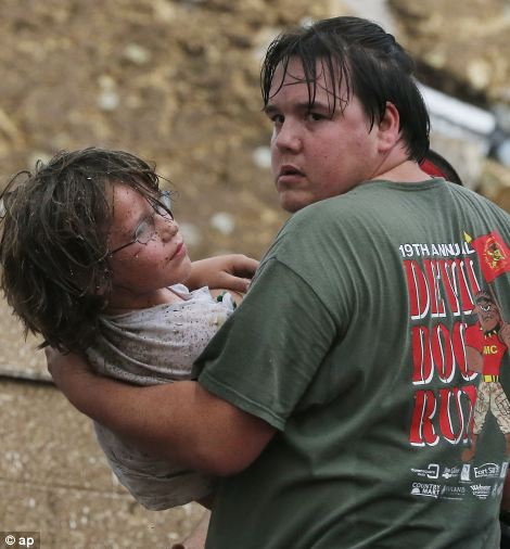 Rescued: An anxious child is carried from the rubble of the Plaza Towers Elementary School