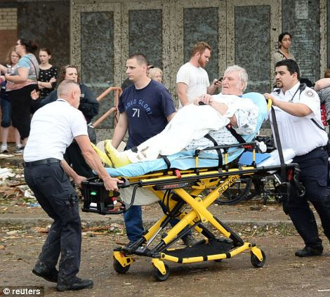 A man is taken away from the IMAX theater that was used as a triage area after a tornado that destroyed buildings and overturned cars struck