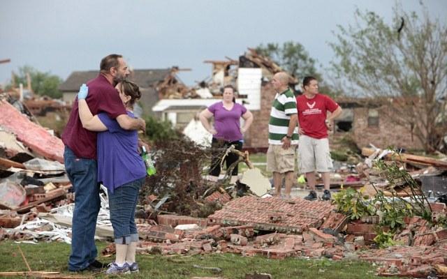 Glenn Rusk hugs his neighbor Sherie Loman outside her home north of Briarwood Elementary School after a tornado moved through the area
