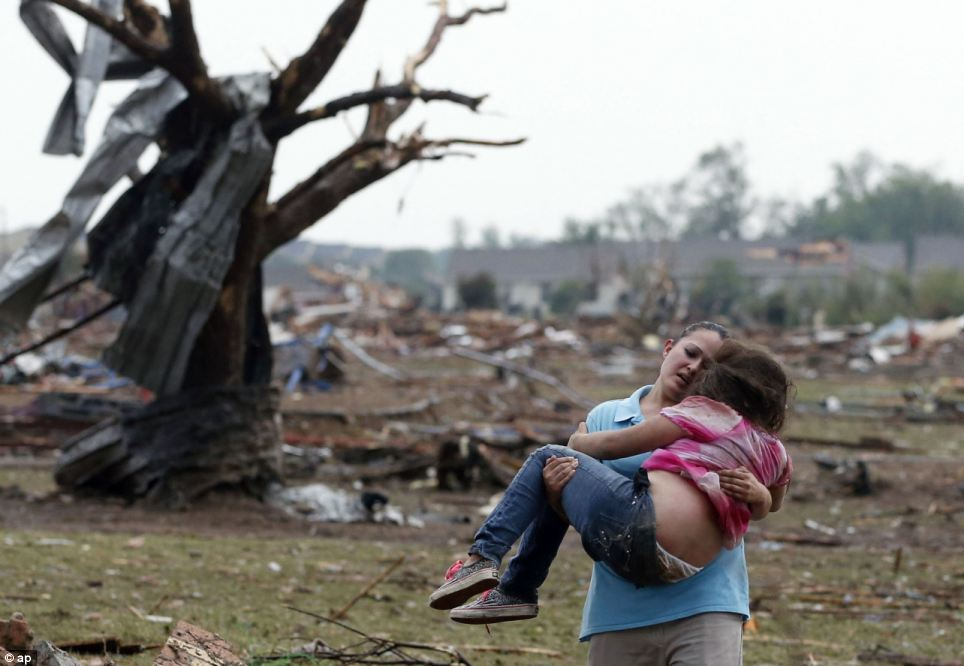 Help: A woman carries a child through a field near the collapsed Plaza Towers Elementary School in Moore
