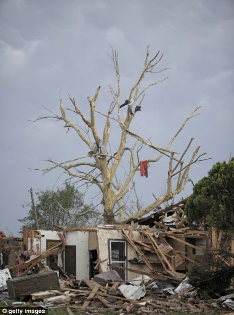Debris hangs from a tree over a destroyed home