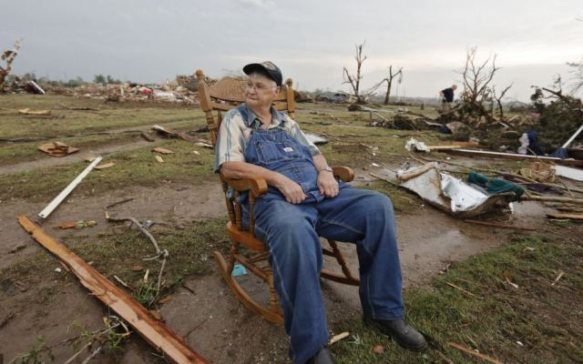 Nothing left: Gene Tripp sits in his rocking chair where his home once stood after being destroyed by a tornado