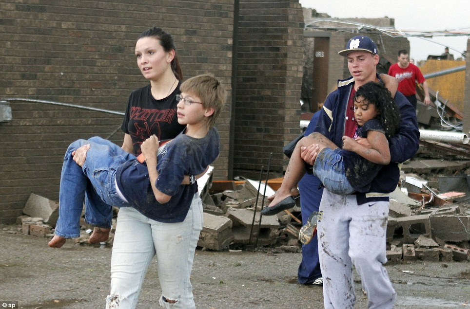Teachers carry children away from Briarwood Elementary school after a tornado destroyed the school in south Oklahoma City