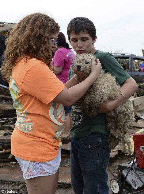Abby Madi (L) and Peterson Zatterlee comforts Zaterlee's dog Rippy
