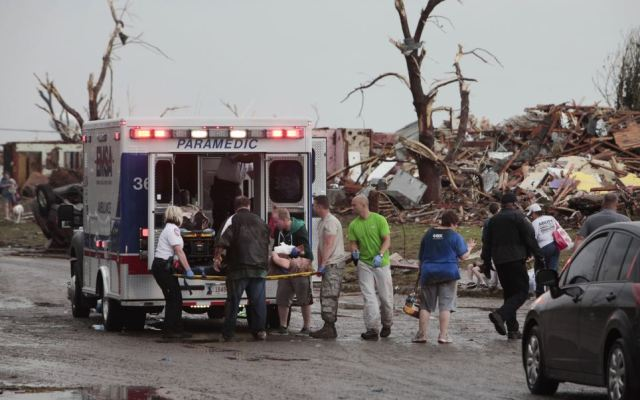 Injured: A tornado victim is loaded in an ambulance in south Oklahoma City after the storm with 200mph winds hit on Monday afternoon