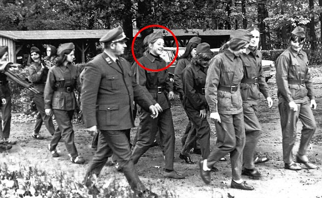 Mrs Merkel (circled) who was 17-year-old Angela Kasner when the picture was taken in 1972, is shown in fatigues marching with a group of friends and an East German officer