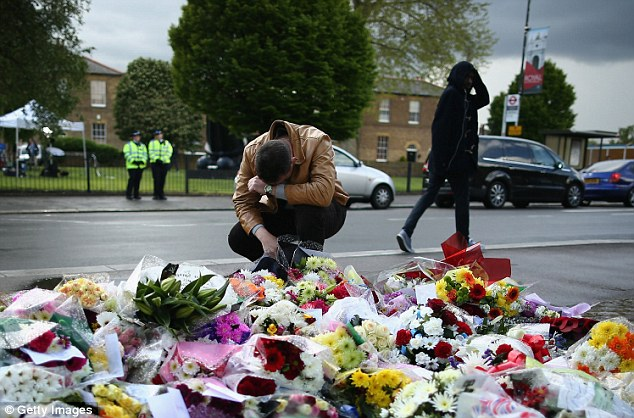 Tearful: A mourner is overcome as he surveys the field of flowers that has been laid in Woolwich in recent days