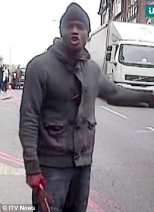 Rant: A man identified as Michael Adebolajo, 28, brandishes a meat cleaver with bloodied hands near the scene of the killing