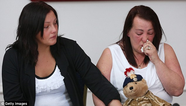 Holding hands: The mother of murdered soldier Lee Rigby, Lyn, is supported by her daughter Sara McClure, whilst she holds a teddy bear bought by Lee for his son, Jack