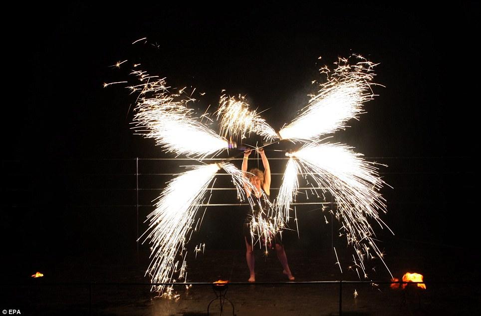 В центре внимания: одного исполнителя одет в черное трико светится от искры, вылетающие из конца два полюса