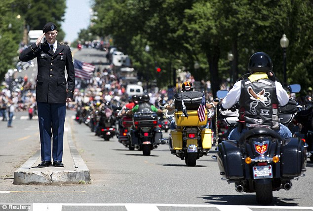 Paying tribute: A U.S. serviceman salutes as hundreds of bikers pass him at the 26th annual Rolling Thunder