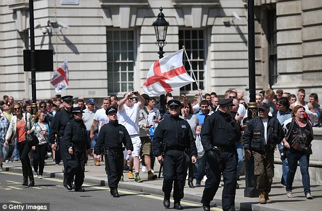 Control: Police officers walk members of the English Defence League as they march from Trafalgar Square