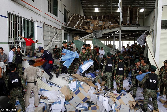 Reduced to rubble: Rescue workers and soldiers search through the site of the accident in a shoe factory in the Kong Pisei district of Kampong Speu province, 30 miles west of the capital, Phnom Penh on May 16