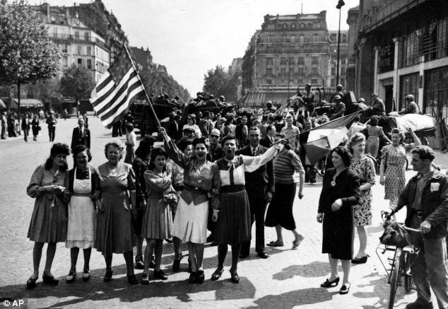 Grateful: French women are seen waving American flags in Paris in August 1944 following the city's liberation, but the book alleges that thousands of French women were raped by GIs after freeing the city from the Nazis
