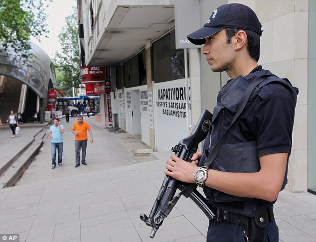Armed officer: A police officer stands on a main boulevard a day after clashes between angry Turkish protesters and security forces in Ankara