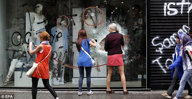 Graffiti: Female shoppers take pictures of damaged store windows covered in spray paint after clashes in Istanbul
