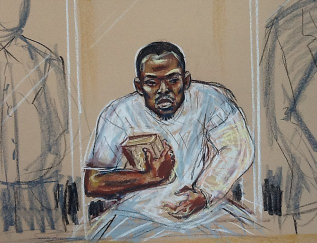 Hearing: Woolwich suspect Michael Adebolajo, whose left arm was heavily bandaged, refused to stand in court this morning and held the Koran throughout