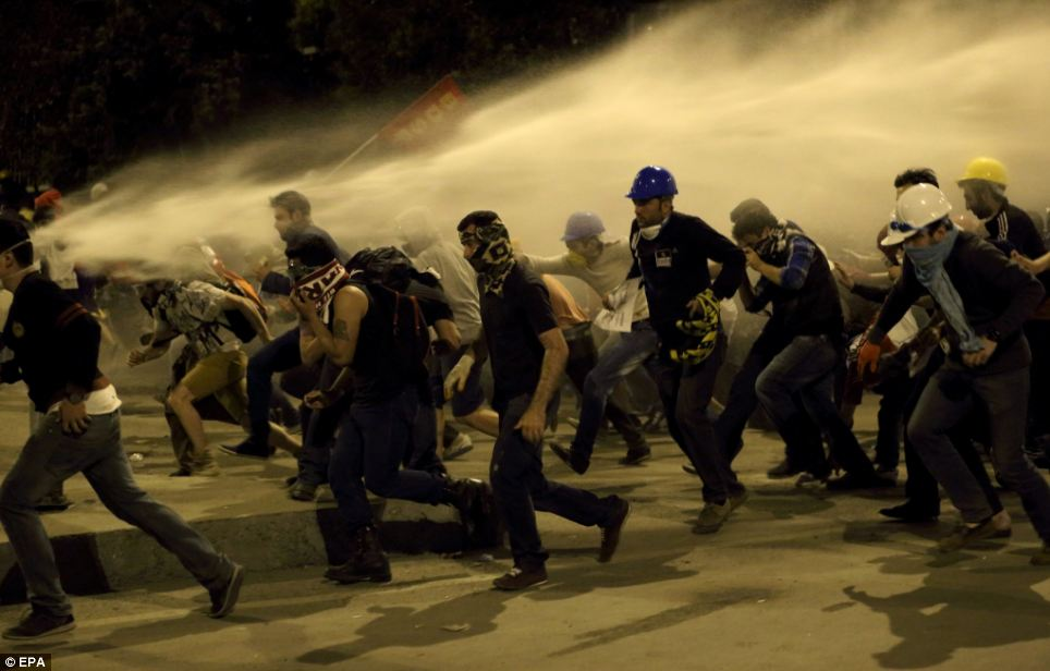 Retreat and regroup: Demonstrators flee the high-pressure spray of a water cannon in an Istanbul street