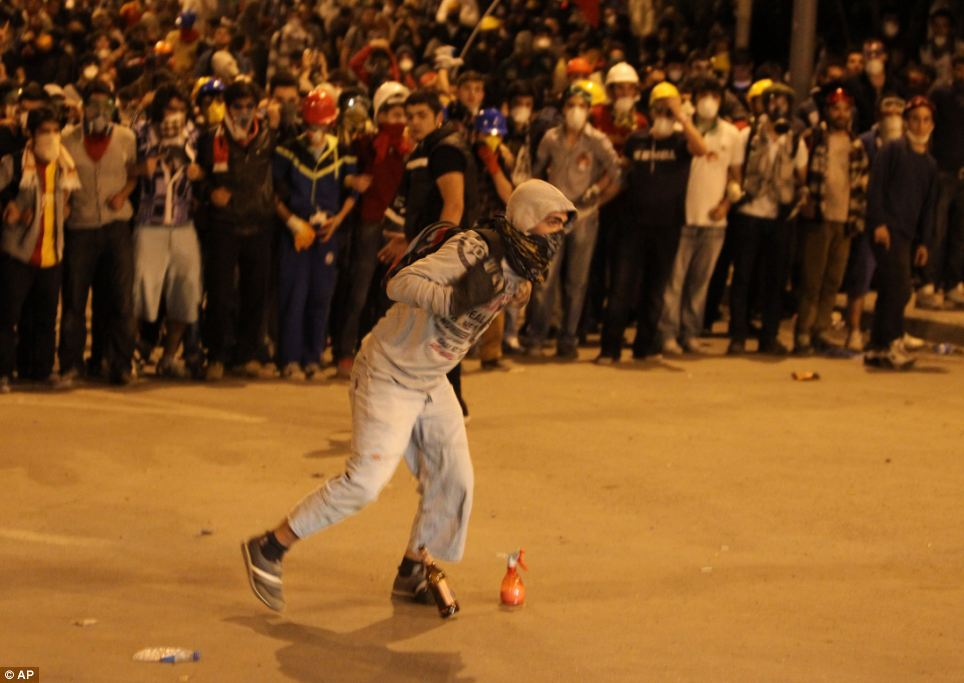 Daring: A brave protester walks towards police lines during a stand-off between demonstrators and police
