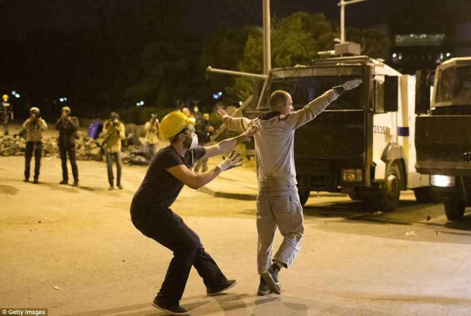Conflict: A protestor tries to prevent his friend from reaching a police water cannon during the clashes