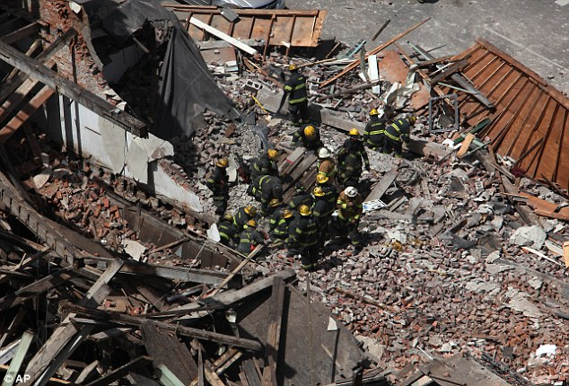 Desperate: A four-story building being demolished collapsed Wednesday on the edge of downtown, injuring 13 people and trapping one other
