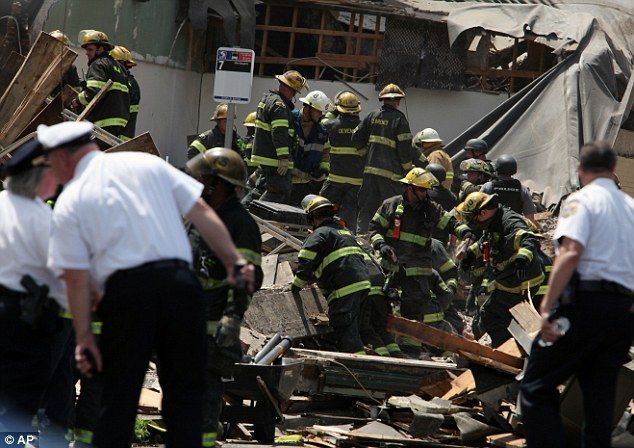 Rescue crews were trying to extricate the two people who were trapped, city Fire Commissioner Lloyd Ayers said