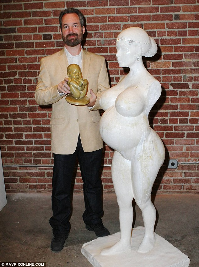 Replica: Edwards posed for a snap cradling his depiction of Kim and Kanye West's unborn fetus as he struck a pose next to his pregnant statue