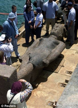 A colossal statue of an ancient unknown Pharaoh lies on a barge in an Alexandrian naval base after it was uncovered in the ancient submerged city of Heracleion