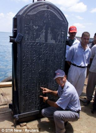 French marine archaeologist Frank Goddio explains text on the stele of Heracleion on a barge in an Alexandrian naval base
