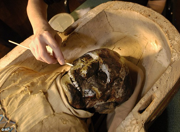 Aging gracefully: Egyptologist Mimi Leveque begins to remove salt deposits from the face of a 2,500 year-old mummy at Massachusetts General Hospital in Boston