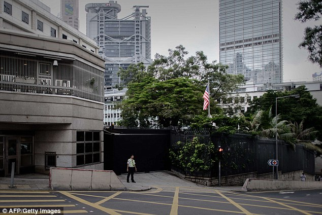 Row: A security guard stands outside the US consulate in Hong Kong today, where inside officials will be trying to extradite Snowden back to the United States