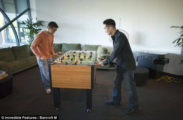 Google employees enjoy a game of Foosball on a break
