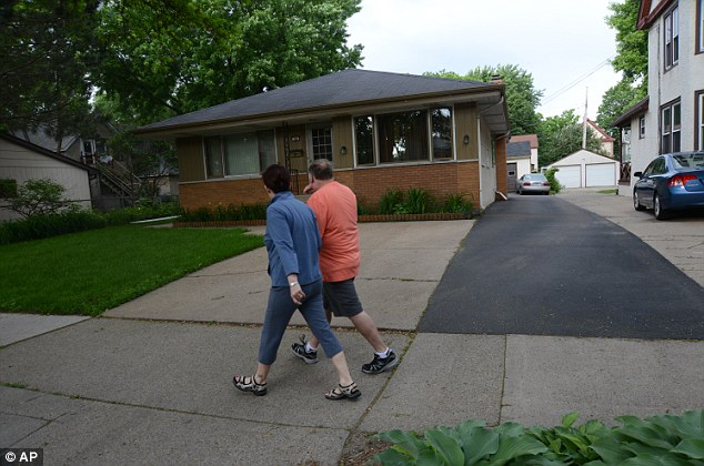 People walk past the home in Minneapolis, Minn., where 94-year-old Michael Karkoc lives