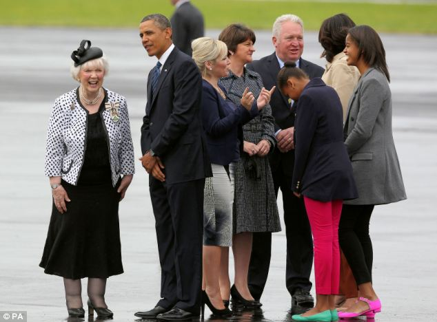 Wet welcome: Sasha laughs as Malia looks down at her feet after arriving in the drizzly weather