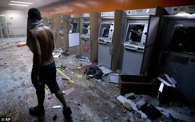 Wrecked: This bank of cash machines in Rio de Janeiro were destroyed by protestors