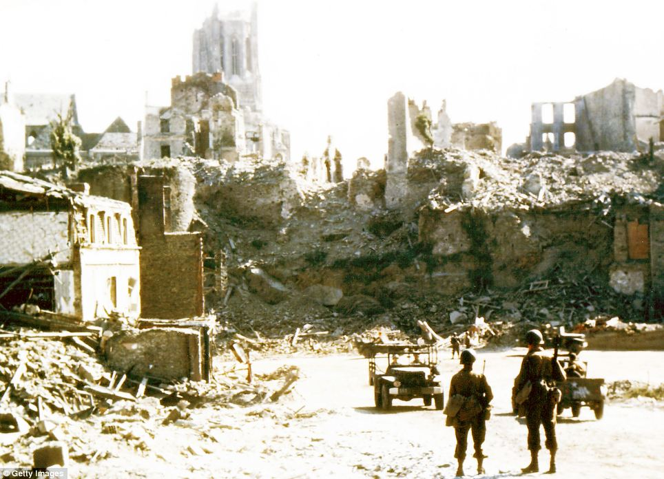 American soldiers watch U.S. Army jeeps drive through the ruins of Saint-Lo, the town was almost totally destroyed by 2,000 Allied bombers when they attacked German troops stationed there during Operation Overlord in June 1944