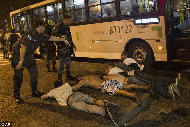 Unrest: A group of protesters lie on the ground as they wait to be searched by police during anti-government demonstrations in Rio de Janeiro, Brazil